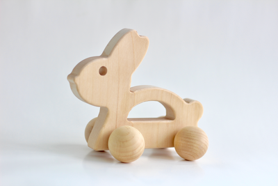 Baby push toy in the shape of a wooden bunny.