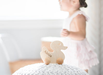 A wooden duck push toy standing on a pouf while a girl is seen walking behind the image of the duck.
