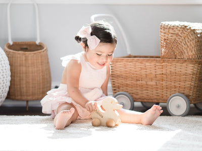 A cute little girl playing with her organic wooden push toy on the floor with her name personalized on the side of it.