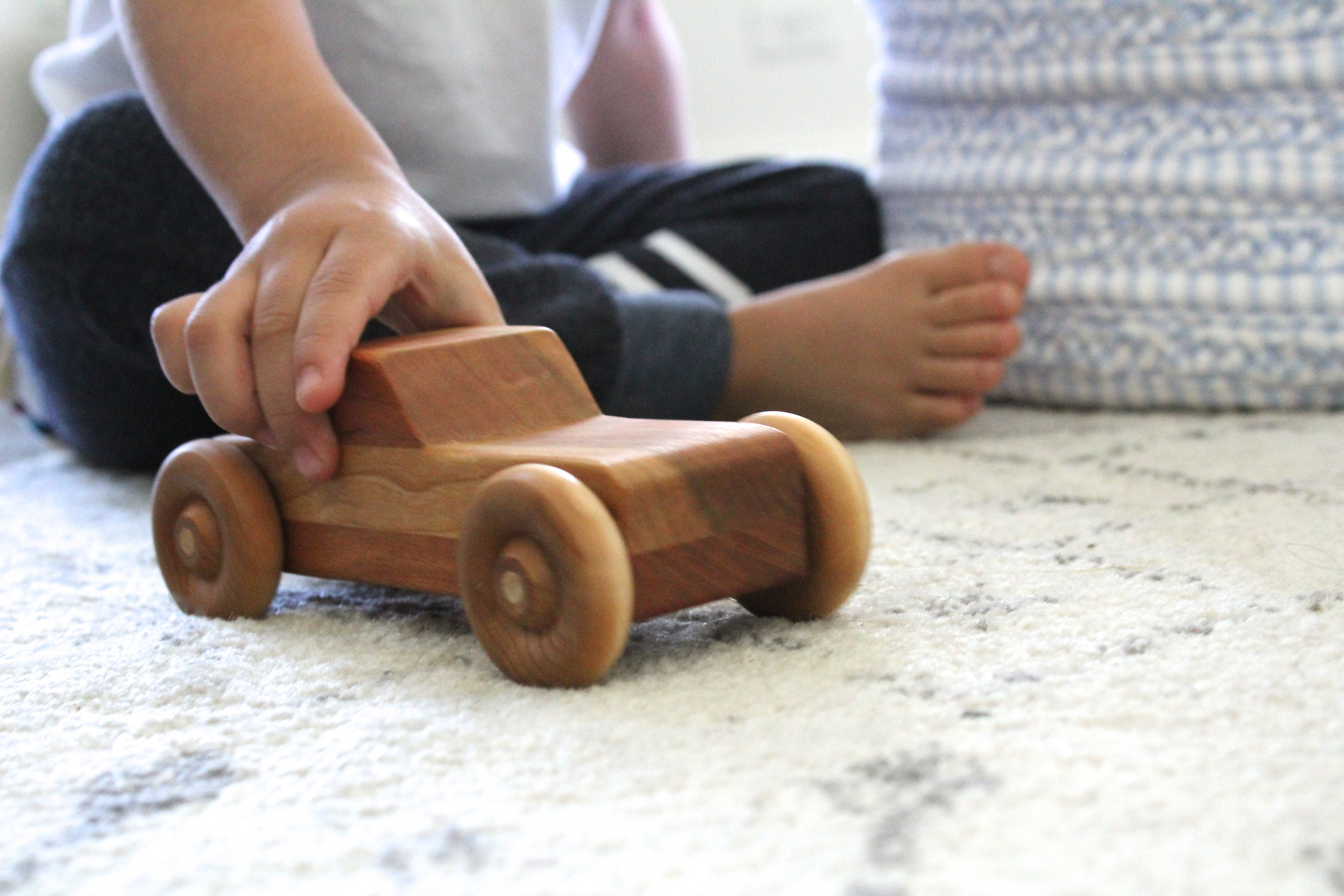 A little boy playing with an heirloom cherry wooden car on the floor.