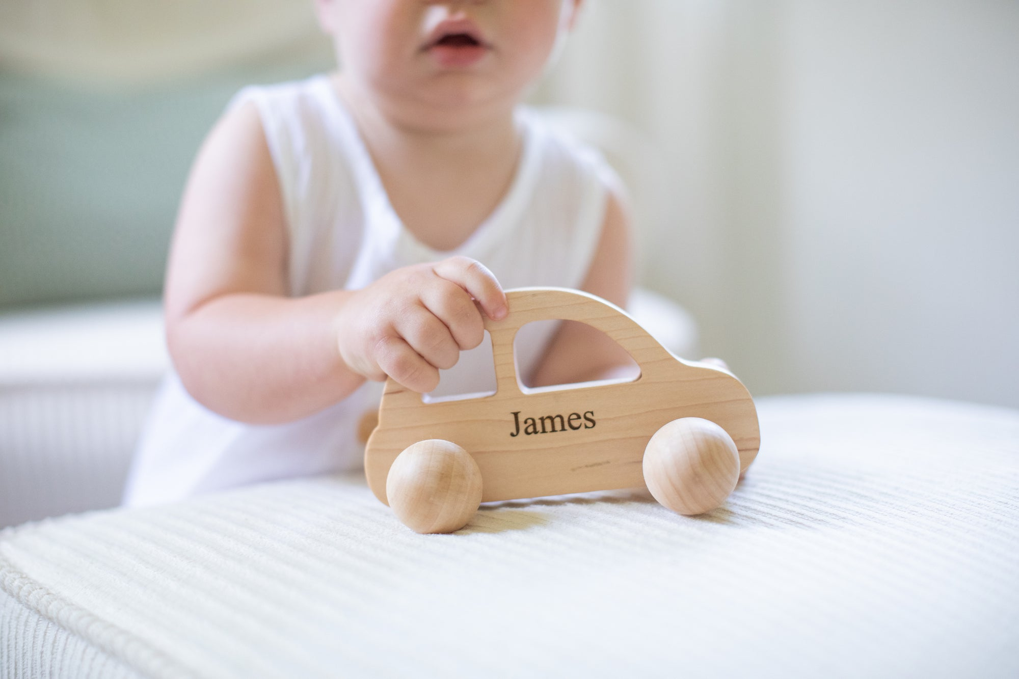 A little cute toddler boy holding a wooden toy car personalized with his name James on it.