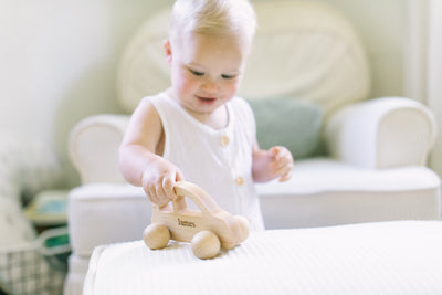 A little boy and his wooden push toy car playing in his nursery room.