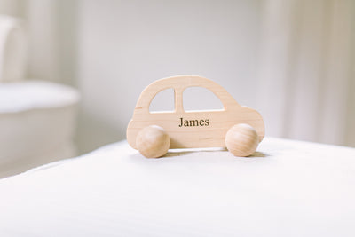 Personalized baby push toy with the name James in a baby nursery.
