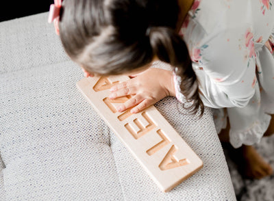 Preschool aged kid using her custom wooden name tracing board.
