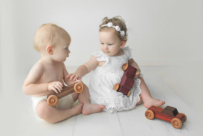 Two adorable babies and toddlers playing with classic heirloom wooden toy cars.