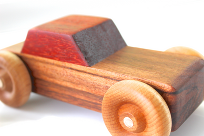 Wooden toy car for children with an orange wooden top.
