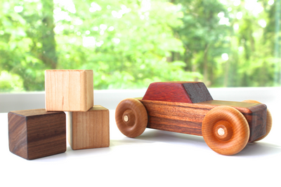 All natural wooden toy car with a stack of organic wooden stacking baby blocks.