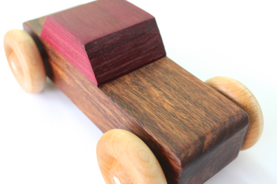 A handmade wooden toy car with a brown body and a purple top using only organic and all natural materials.
