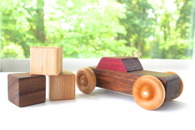Children's wooden toy car with a brown body and a purple top.