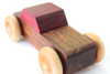 Handmade wooden toy car with a brown body and a purple top made using only all natural and organic materials.