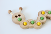 Wooden ten frame in the shape of a caterpillar with yellow and green marbles.