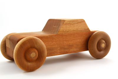 Wooden toy car with four wheels in cherry wood.