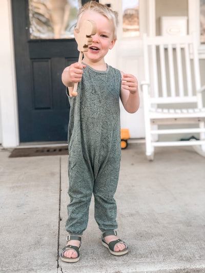 An adorable little boy holding his wooden Dino wand in the air for pretend play.