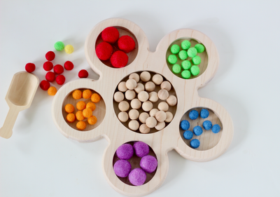 Loose parts tinker tray in the shape of a flower for fun independent creative play.