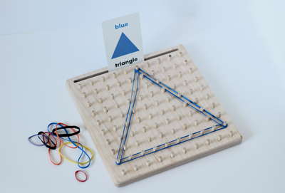 Wooden geoboard for early learning with rubber bands and notecards.
