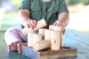 A little baby girl playing with a wooden shape sorter made out of organic hardwood.