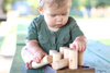 Organic wooden shape sorter being played with by an adorable little baby girl.