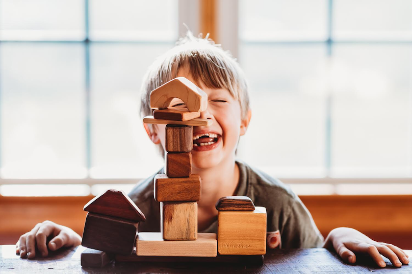 A little boy playing with wooden building blocks and creating a village.