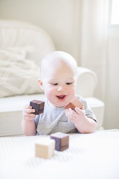 An adorable baby boy laughing while playing with classic wooden stacking blocks.