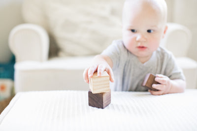 A cute baby playing with wooden baby stacking  blocks and stacking them on top of one another.