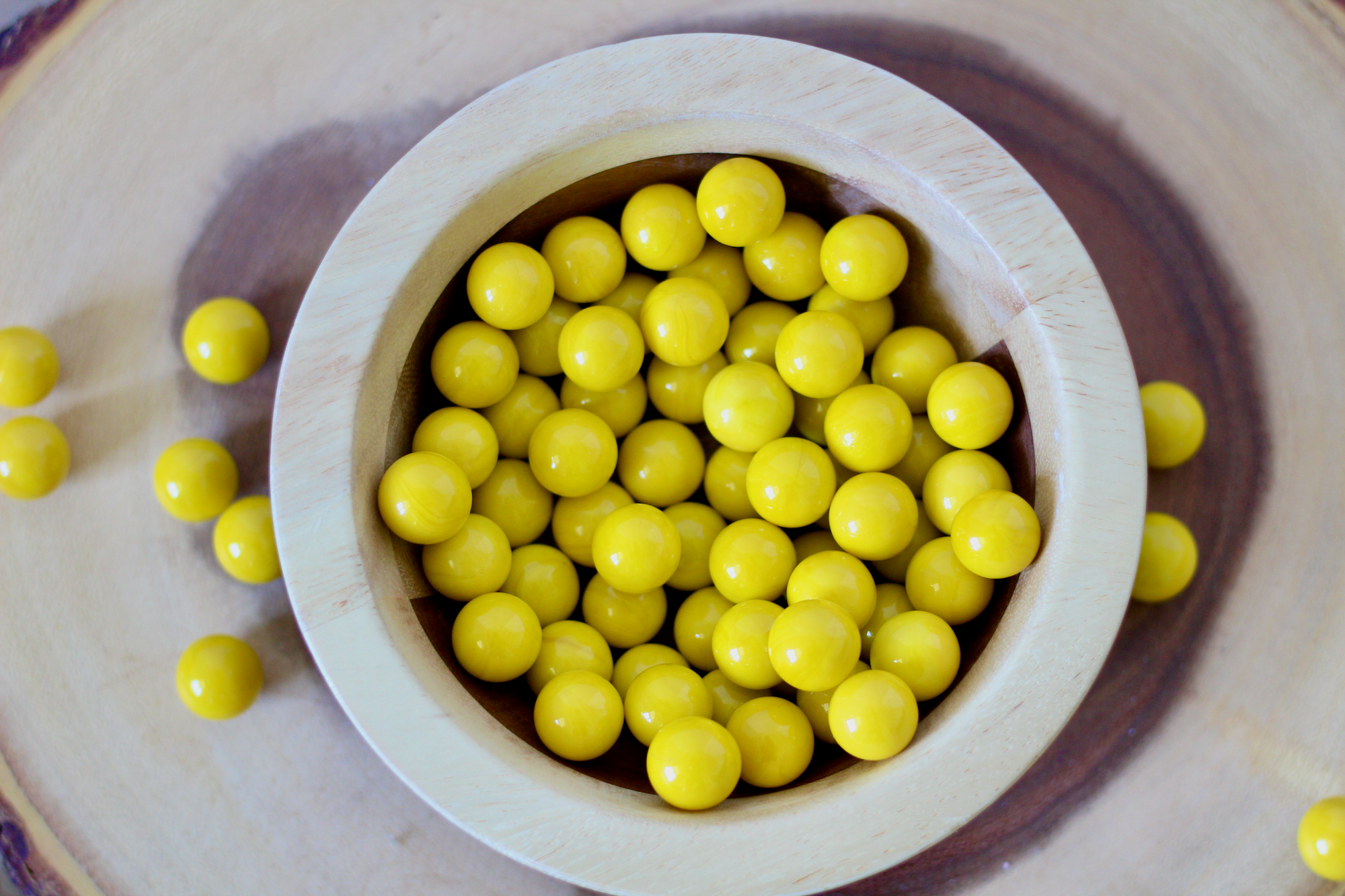 Yellow marble manipulatives for montessori homeschooling and sensory play.