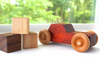 Organic orange wooden toy car next to all natural wooden baby blocks.