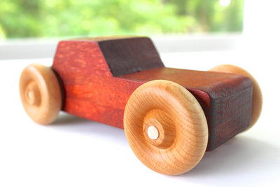Children's orange wooden toy car made with all natural materials and without any paints or dyes.