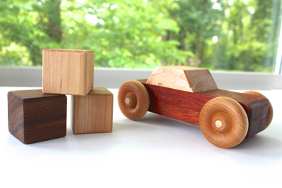 Wooden toy car sitting near wooden baby blocks.