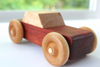 Handmade wooden toy car in an orange body and modern beige top.