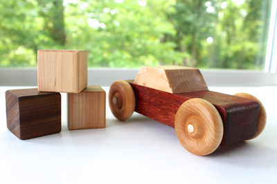 Handmade wooden toy cars near a stack of baby blocks.