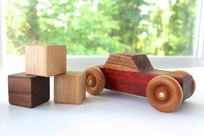 Wooden toy cars for kids displayed next to a stack of baby blocks.