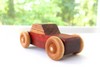 Wooden toy car with an all natural wooden orange body with a brown and black striped wooden top.