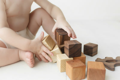 A baby playing with tricolored wooden stacking blocks.