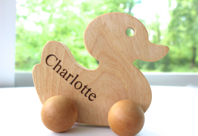 Wooden push toys for toddlers in the shape of a duck with the personalized name Charlotte.