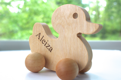 Kids wooden push toy duck with personalized name.