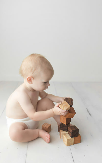 A cute baby boy wearing only a diaper playing and stacking wooden toy blocks of different colors and textures.