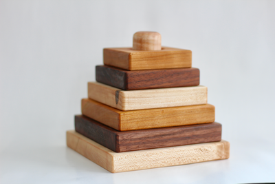 Square stacking toy made out three different types of hardwoods like Cherry, Walnut, and Maple.