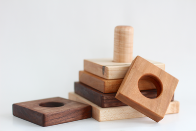 Square wooden stacking toy spread out over the floor in three different types of hardwood.
