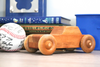 Wooden toy car on a shelf in a boys room.