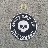 "A machine embroidered patch on black duck canvas.  Circular in shape with a white stitched border, a cartoonish human skull with no lower jaw is circled by the words ""Every day is Halloween"" in typewriter style font.  All stitching done in white thread. A US quarter is shown for scale."