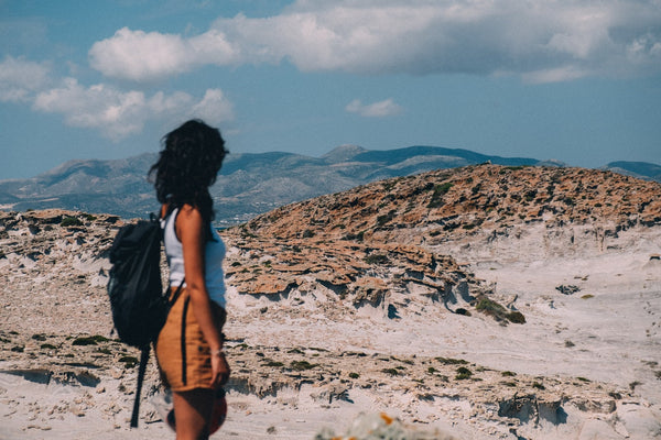 A woman in a backpack hikes in an arid landscape