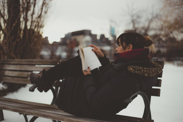 A young woman reads a book on a snowy bench in a parka