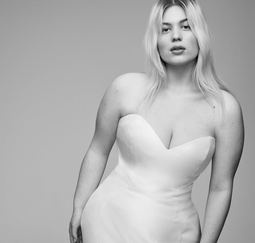 Plus size model standing while wearing a Curve Couture minimal trumpet wedding gown of architectural seamlines.