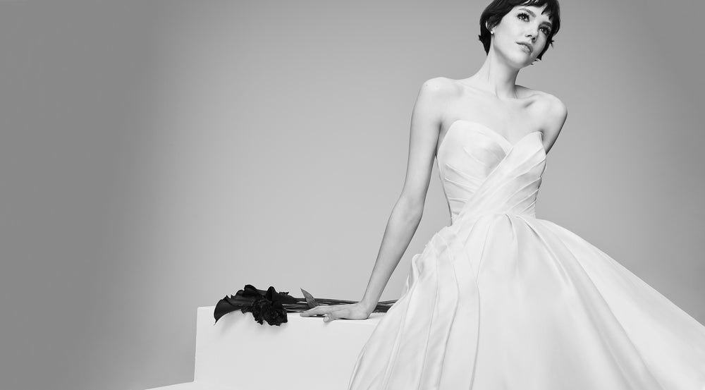 Model sitting down wearing a sweet heart strapless wedding ballgown.