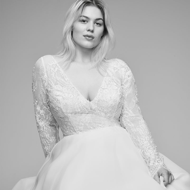 Model wearing long sleeve lace wedding gown with front and back deep v-neck lines and full a-line skirt.