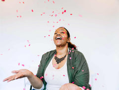 brown skinned woman laughs with head tilted back with pink circular confetti rains down