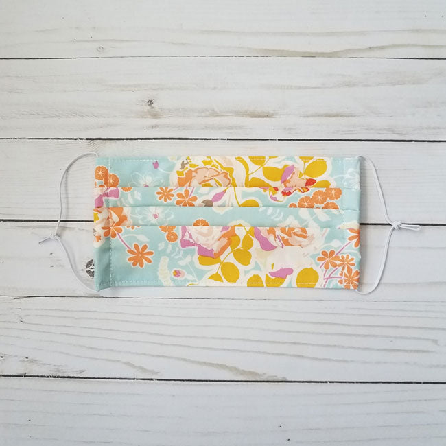 Handmade premium 100% cotton reusable fabric face mask pleated with adjustable elastic in vibrant pink, yellow, and aqua blue floral print