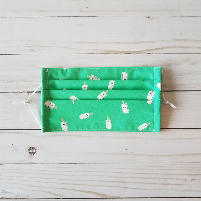 Handmade premium 100% cotton reusable fabric face mask pleated with adjustable elastic in white popsicles on bright green print