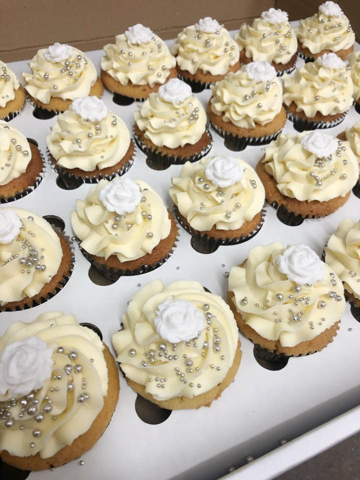 Vanilla Cupcake decorated with white roses and silver sprinkles and jam inside