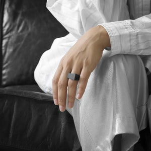 A person wearing the MK3 Ring on their ring finger while sitting on a black leather sofa